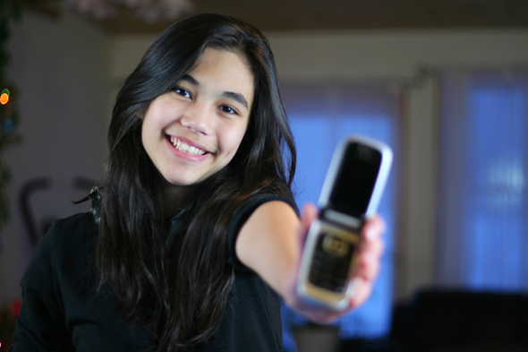 Young teen girl proudly holding out her first cell phone.